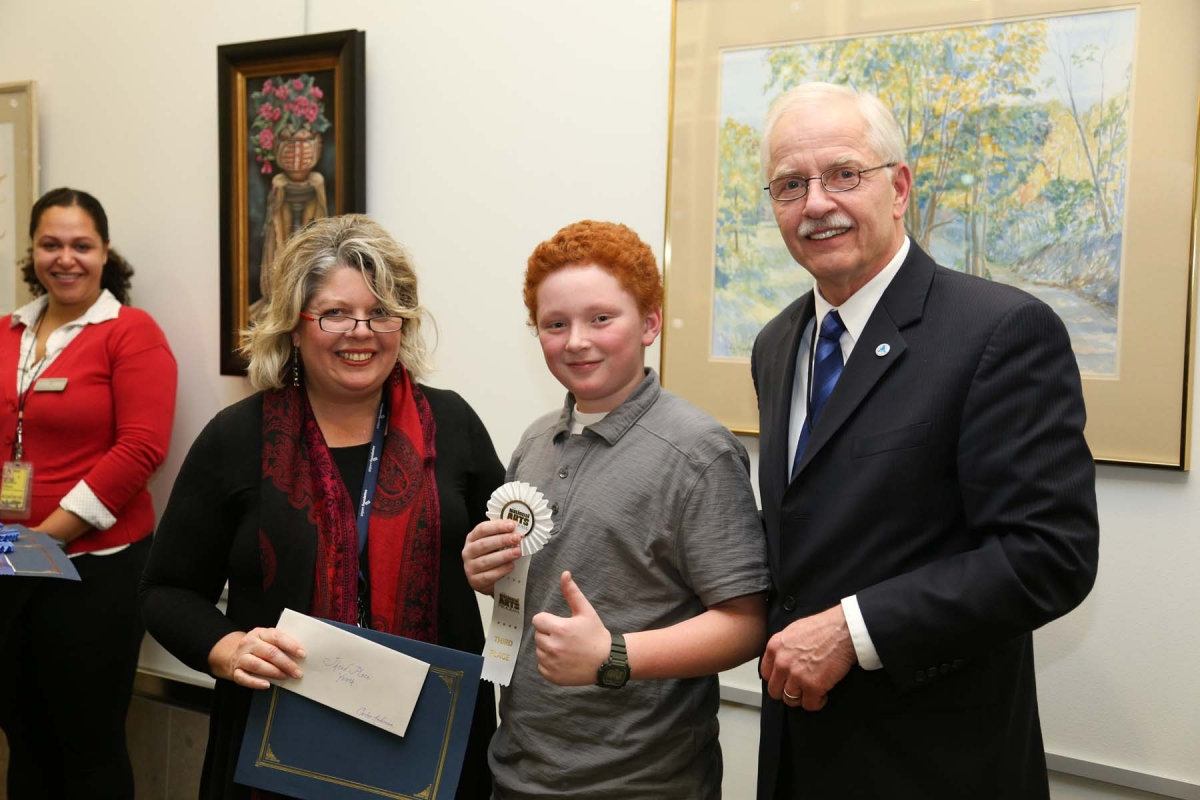 Jana Vaughn, Executive Director of the Airport Foundation MSP and Jeff Hamiel, Executive Director and CEO of the Metropolitan Airports Commission pose with Youth Artist Carter Anderson, who took home the Third Place Prize for his painting entitled 'Base Hit'.