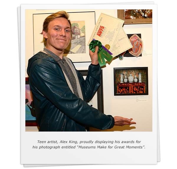 "Teen artist, Alex King, proudly displaying his awards for his photograph entitled ""Museums Make for Great Moments""."