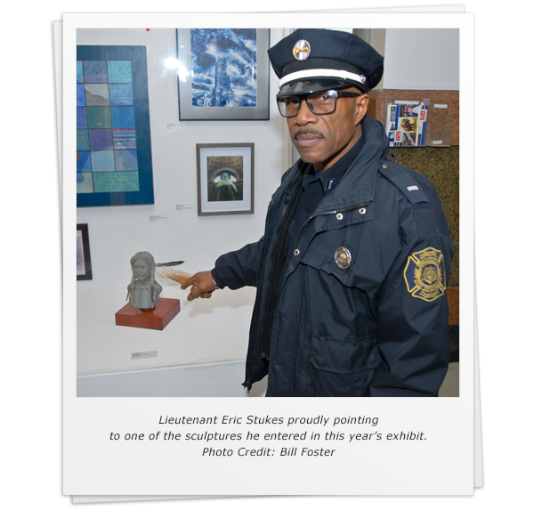 Lieutenant Eric Stukes proudly pointing to one of the sculptures he entered in this year's exhibit. Photo Credit: Bill Foster