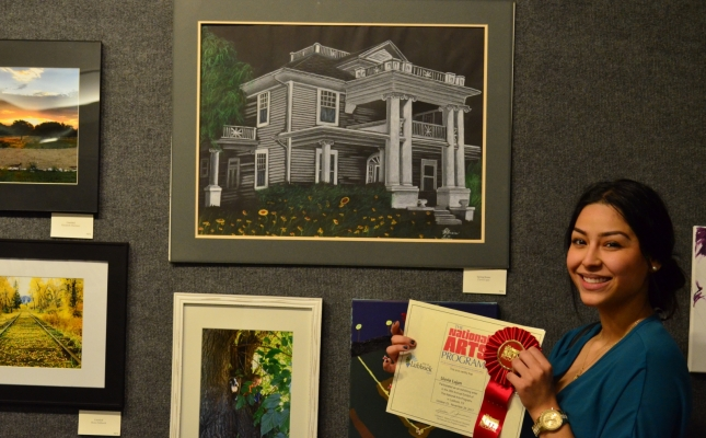 """Second Place Award Winner, Lluvia Lujan, from the Amateur category, poses next to her beautiful work entitled """"Spring House""""."""