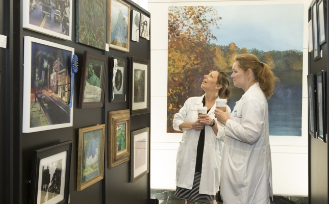 Two nurses take time out of their hectic schedule to stop and enjoy all the artwork made by fellow employees and their family members