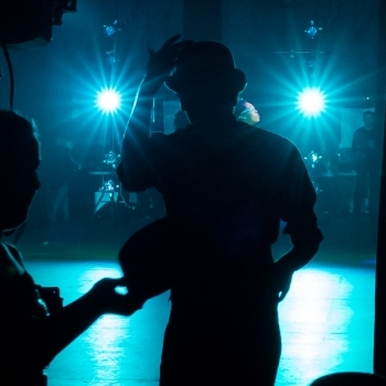 Silhouette of dancer exiting stage with spotlights