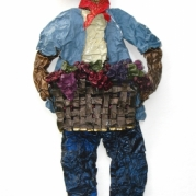A sculpture on paper made from wine capsules of a field worker carrying a basket of grapes