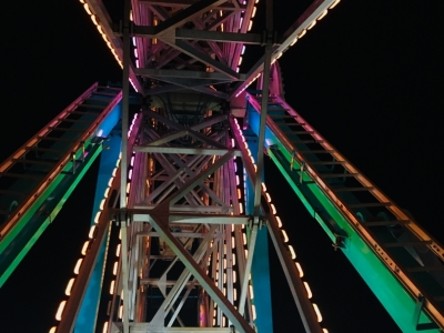 A view of the lit-up structure of the ferris wheel at night while riding the ferris wheel