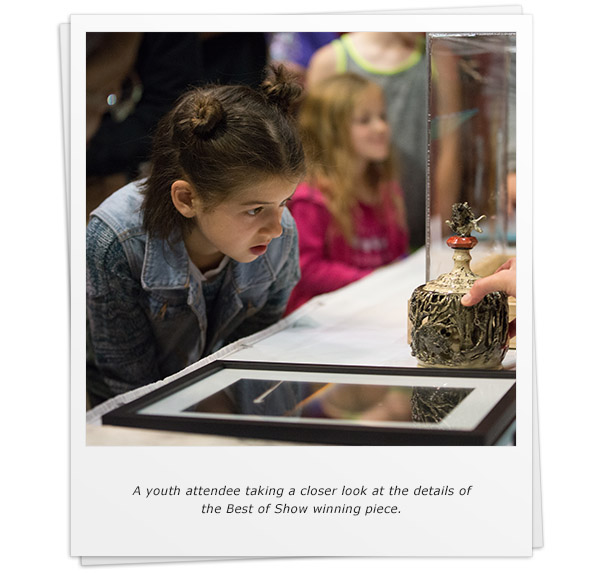 A youth attendee taking a closer look at the details of the Best of Show winning piece.